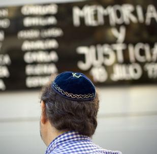 Un hombre junto a la sede de la Asociación Mutual Israelita Argentina en Buenos Aires