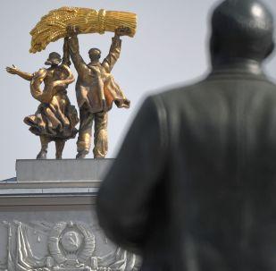 La estatua del conductor del tractor y la agricultora de la granja colectiva (koljosiana) en el arco de la entrada principal a la Exposición los Logros de la Economía Nacional en Moscú.