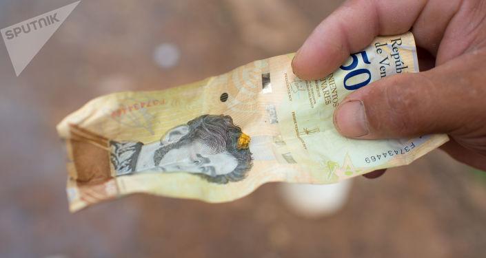 Una pepita de oro en un billete de bolívaro