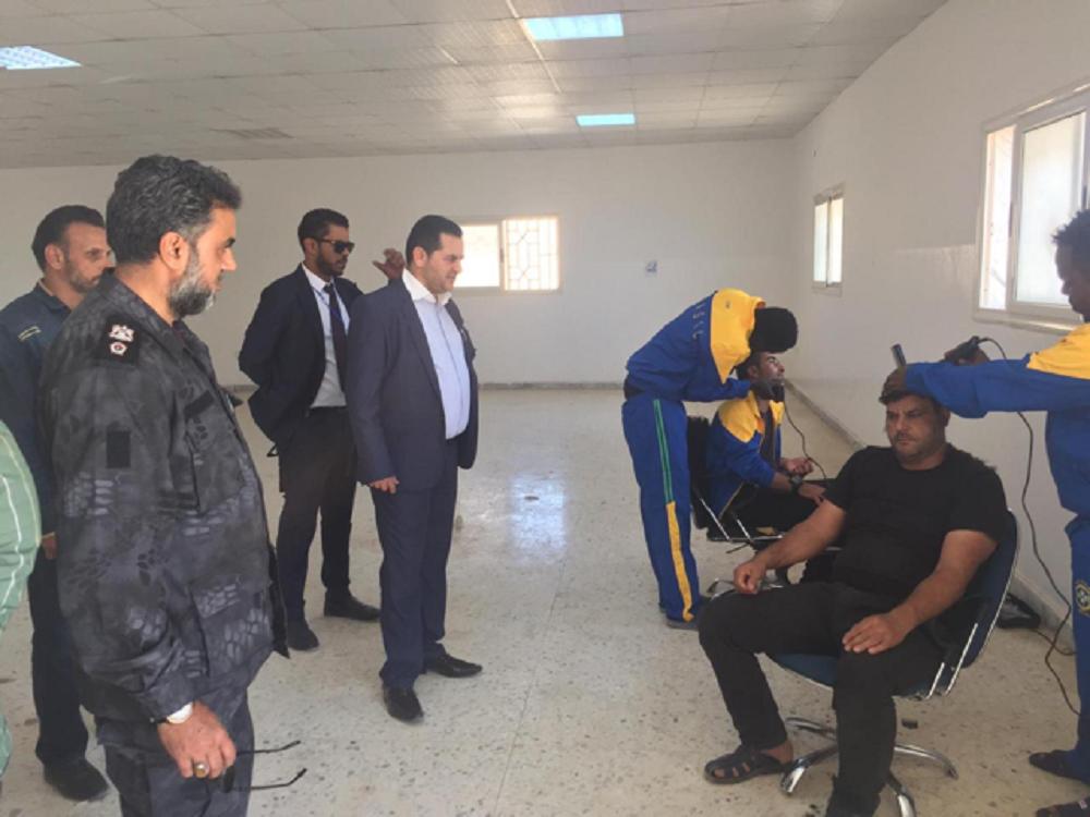 Migrantes cortándose el pelo en el centro de detención de Ganfouda