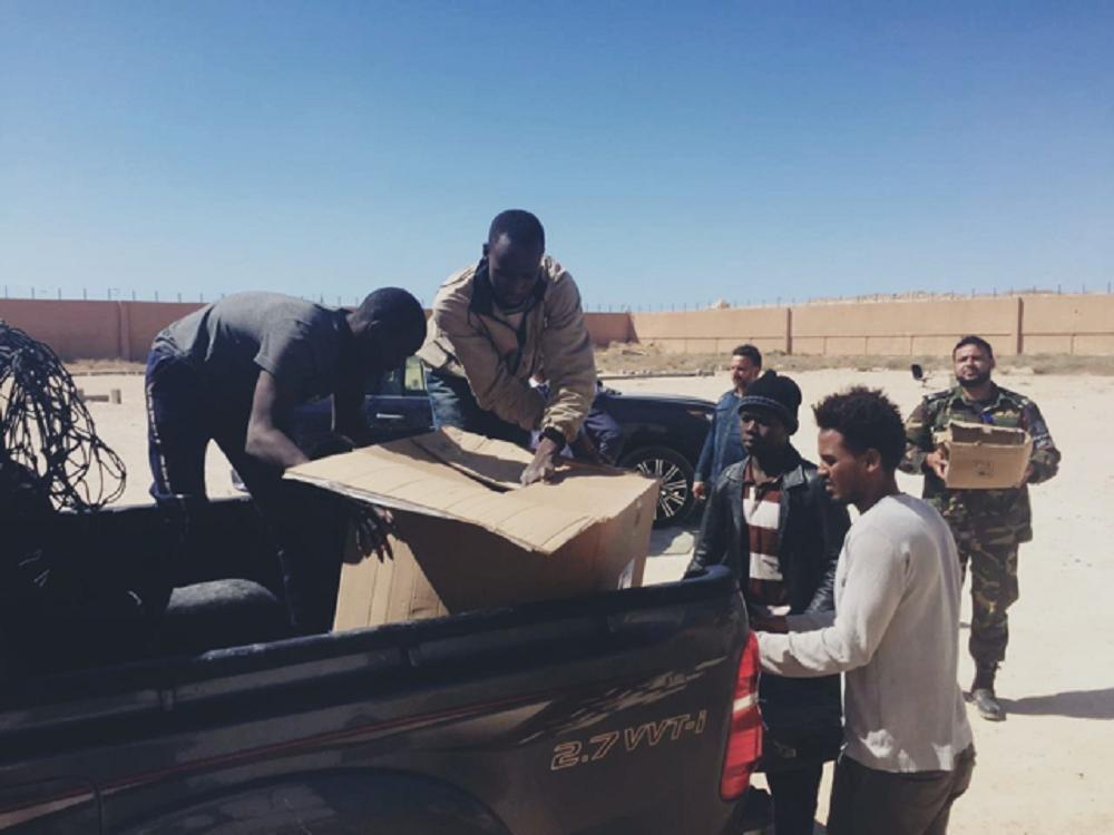 Migrantes descargando una camioneta en el campamento deGanfouda