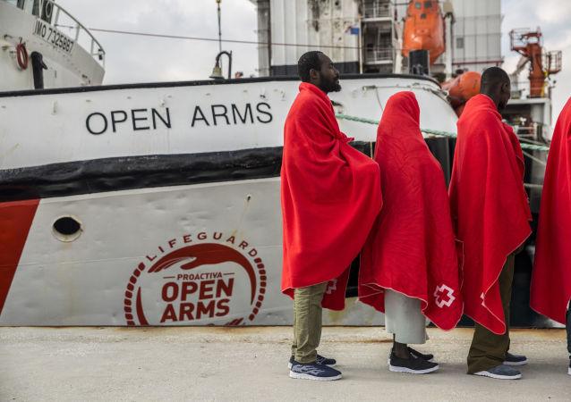 Migrantes cerca de un barco