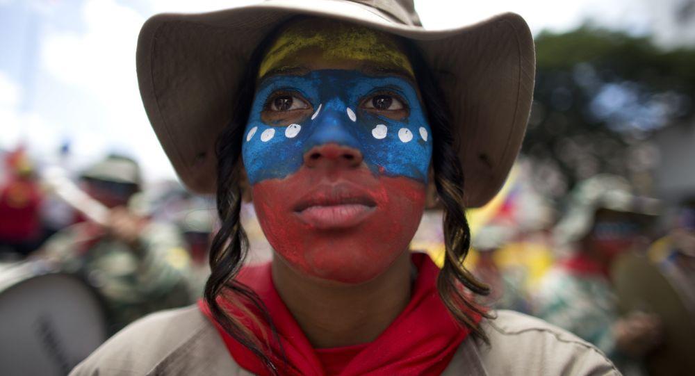 Una mujer con el rostro pintado con los colores de la bandera de Venezuela