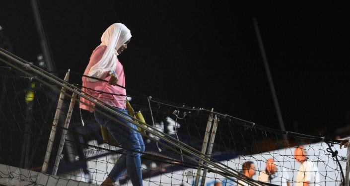Una mujer bajando del Open Arms en Lampedusa