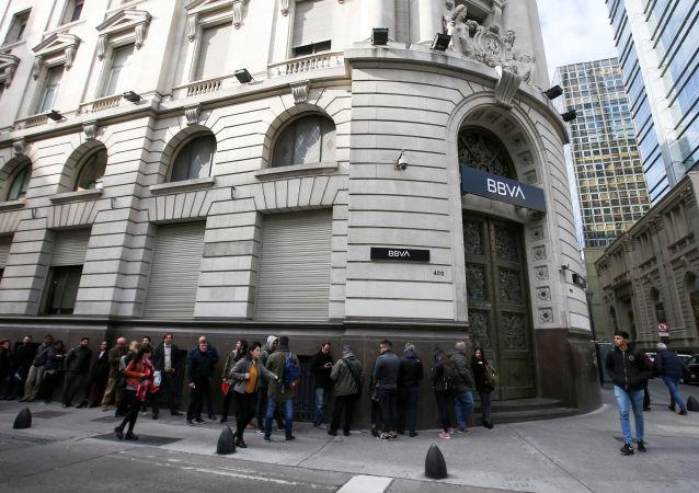 Un grupo de personas hacen fila en las afueras del banco BBVA en Buenos Aires