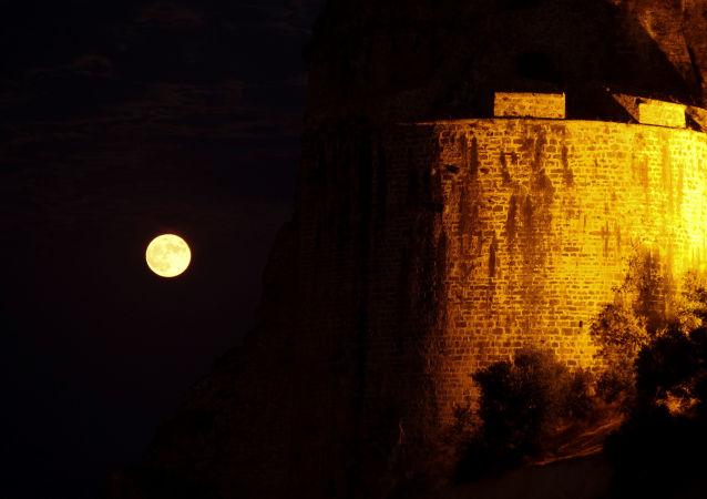 Una luna llena sale junto al castillo veneciano de la ciudad de Koroni, Grecia.