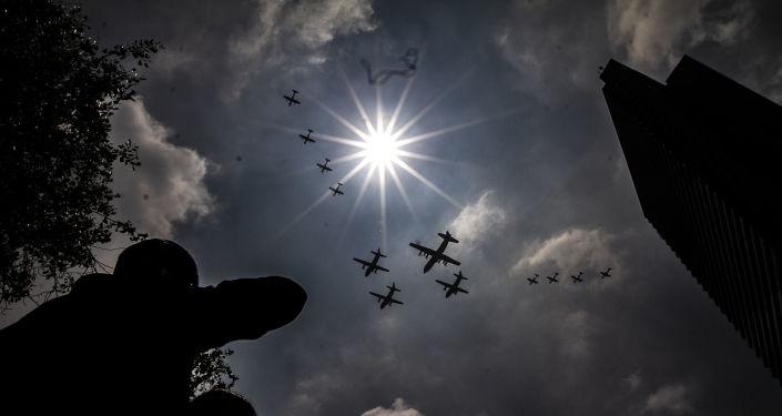 Asistentes observan el desfile de aeronaves de las Fuerzas Armadas Mexicanas
