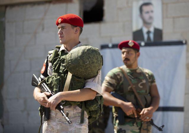 Un soldado ruso y otro sirio ante el retrato del presidente Bashar Asad