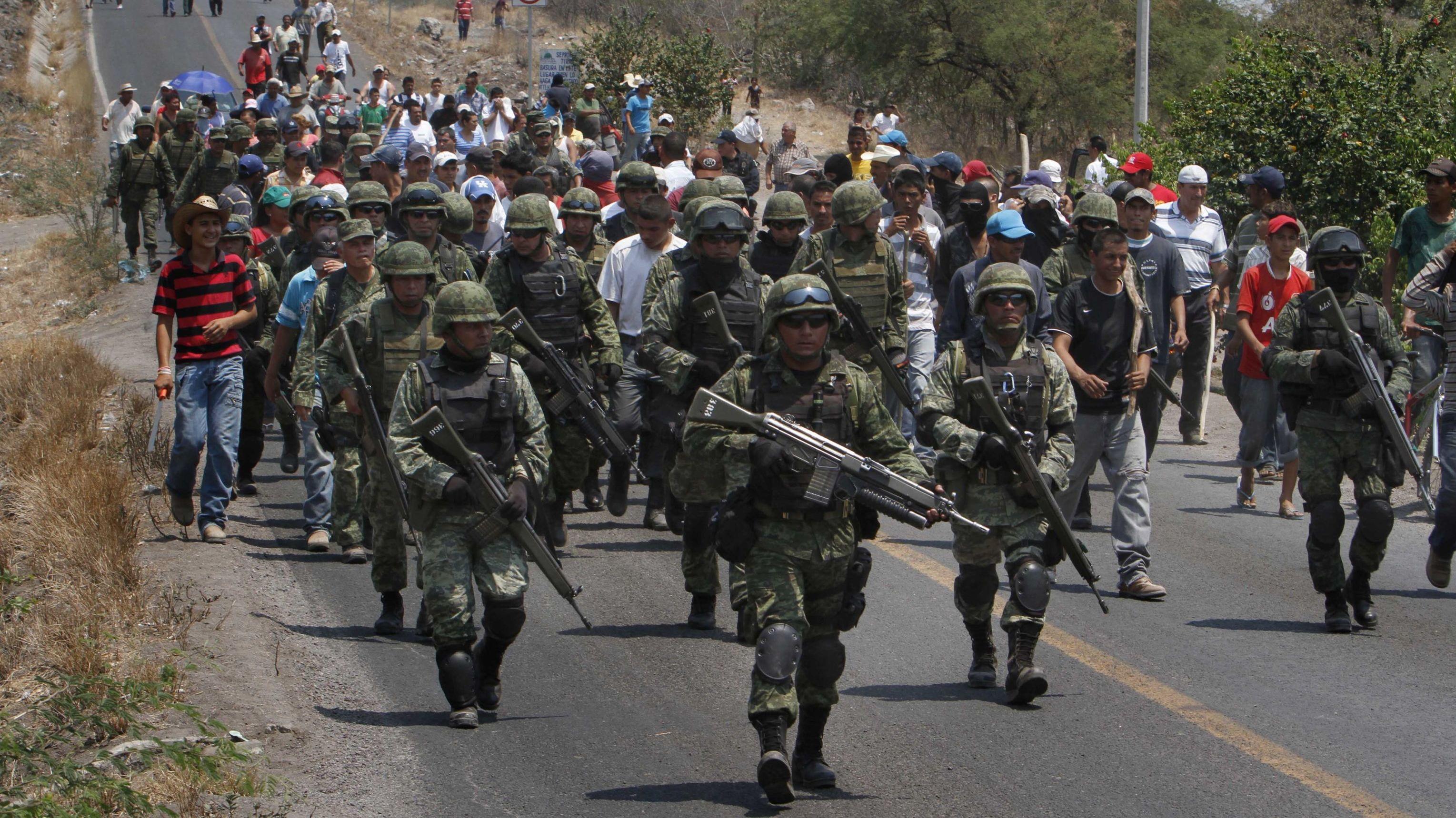 Soldados mexicanos son escoltados por autodefensas de la ciudad de Buenavista que hacen resistencia a los grupos criminales locales