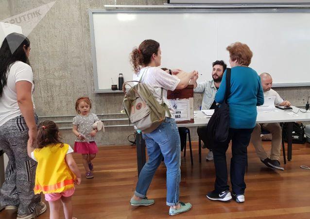 Sufragantes emitiendo su voto en el circuito 463 de la Escuela Universitaria Técnica Médica, Montevideo