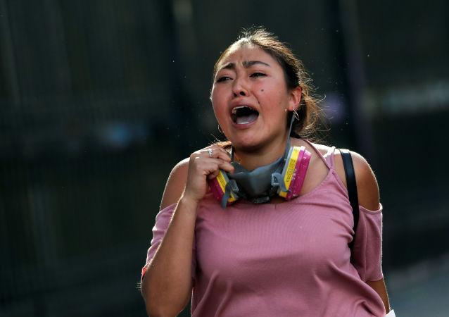 Una mujer chilena corre durante las protestas en Santiago