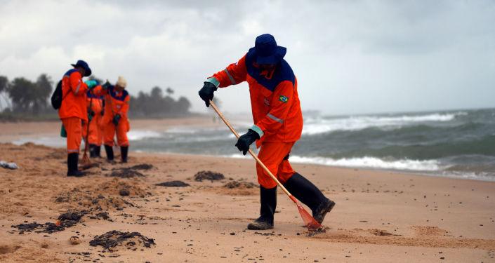 Trabajadores municipales limpiando de petróleo la playa de Barra de Jacuipe en Camacari