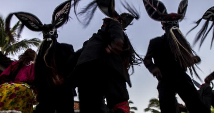 Diablos danzan en un hogar durante el Día de Muertos