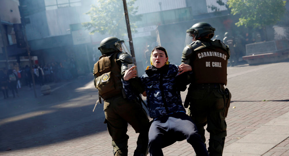 Carabineros de Chile atrapan a un manifestante durante una protesta