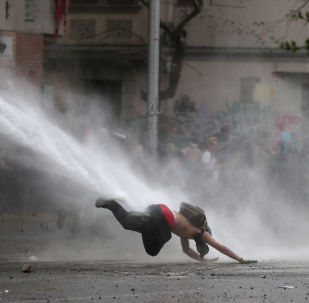 Un manifestante cae al suelo por un tanque de agua durante las protestas en Chile (archivo)