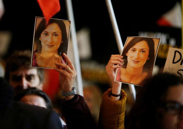 La gente sostiene las fotos de la periodista Daphne Caruana Galizia