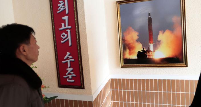 Un hombre mira la foto del lanzamiento de un misil norcoreano
