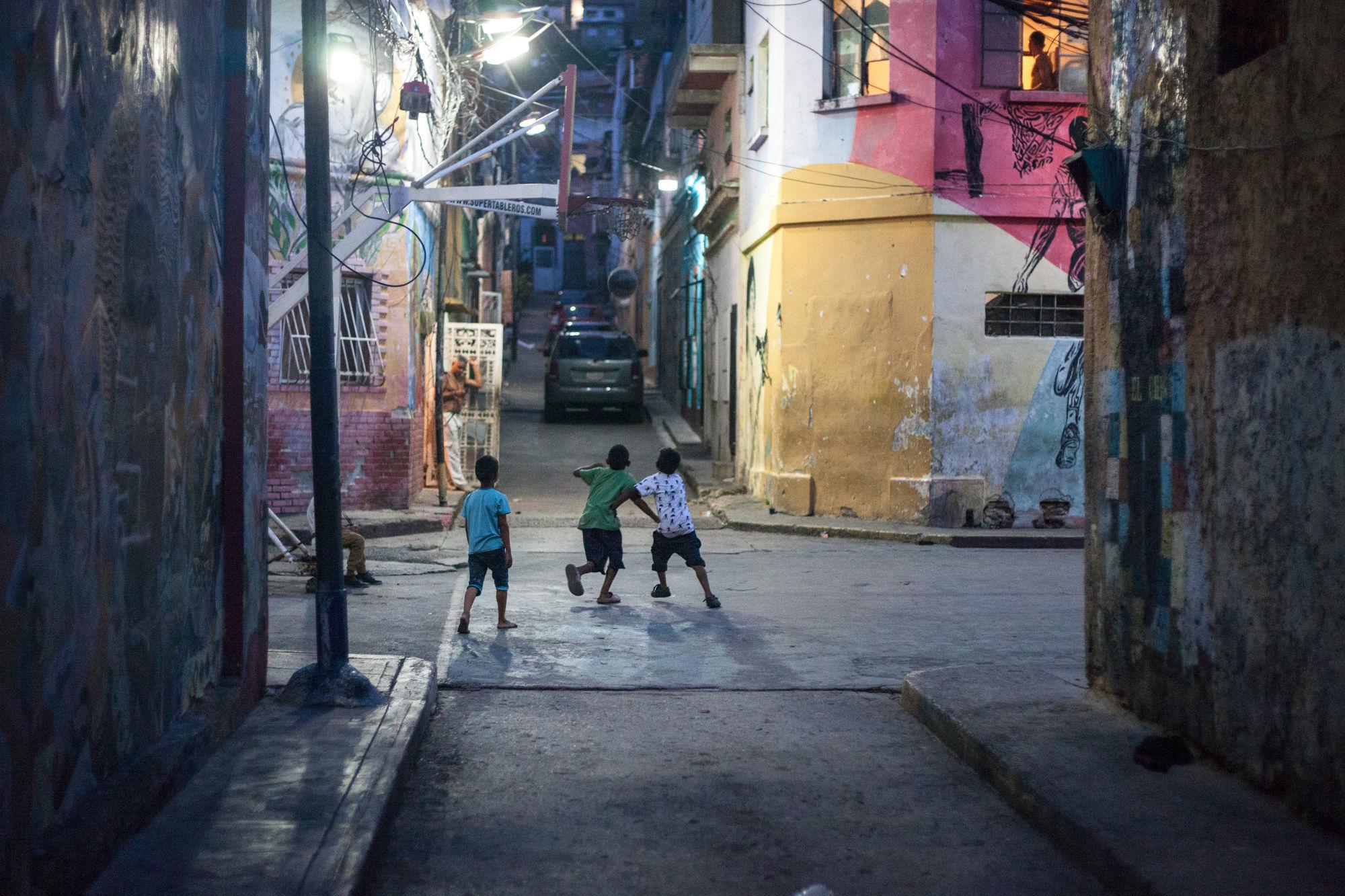 Niños jugado con pelota en la noche de Caracas