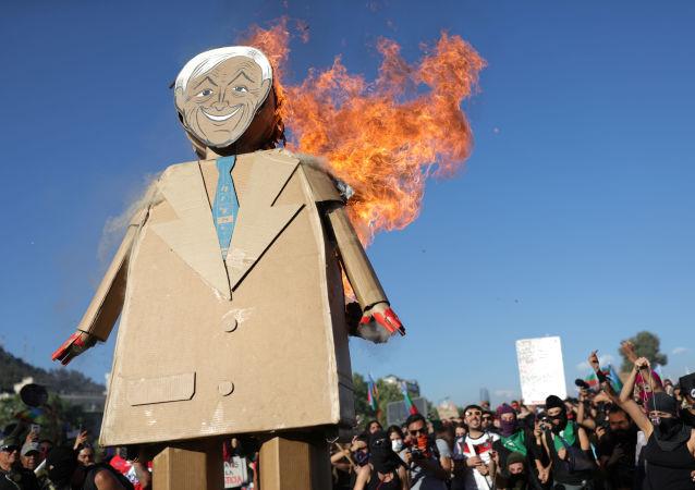 Figura de cartón del presidente chileno, Sebastián Piñera, incendiada por manifestantes