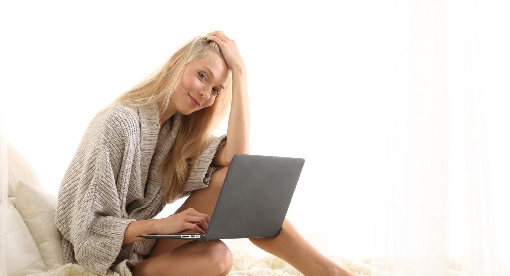 Una mujer utiliza su computadora en la cama