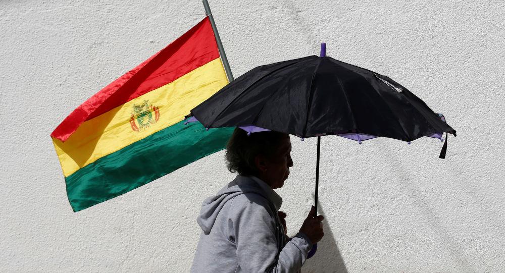 Una mujer con un paraguas y una bandera de Bolivia