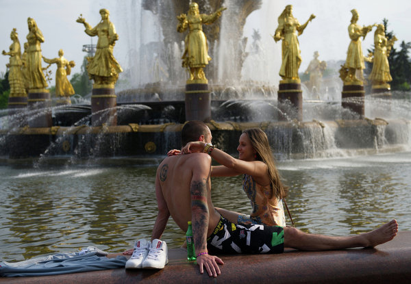 Молодые люди отдыхают у фонтана Дружба народов на территории ВВЦ в Москве