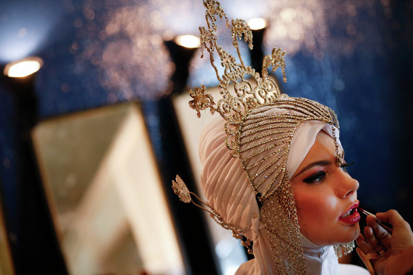 Модель за кулисами перед выходом на подиум во время фестиваля Исламской моды в Куала-Лумпуре