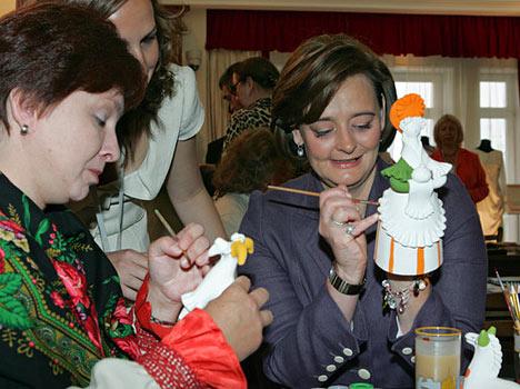 Las esposas de los líderes del G8 pintaron en Strelna varias obras de porcelana, madera y cerámica, así como visitaron una exposición de artesanías únicas de Palej, Jojloma, Gzhel y Bogorodskoe, pudieron deleitarse con la producción de la Fábrica Imperial de Porcelana y obras de los alumnos de la Escuela Superior de Artesanos de San Petersburgo. Esposa del primer ministro de Gran Bretaña, Cherry Blair, durante la visita a la feria de artesanías rusas. Strelna.