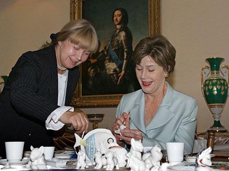 Lora Bush escogió una gata de porcelana, después de haber pintado también un plato y una cuchara de Jojloma. Esposa del presidente de EEUU, Lora Bush, durante la visita a la feria de artesanías rusas. Strelna.