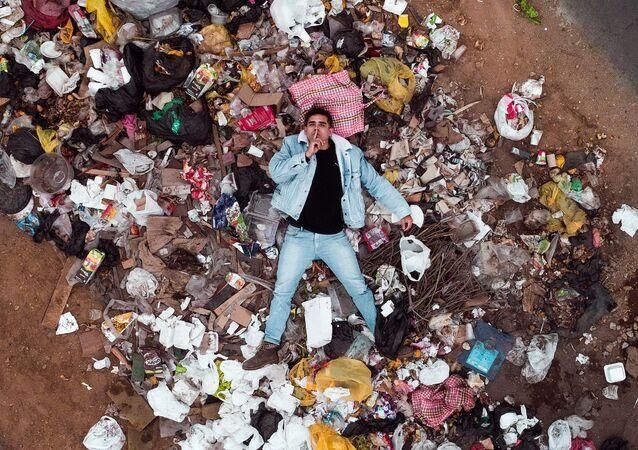 Un hombre entre la basura de plástico
