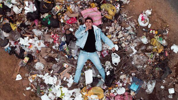 Un hombre entre la basura de plástico - Sputnik Mundo