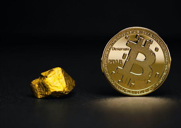 Una pepita de oro y un bitcoin (imagen referencial)