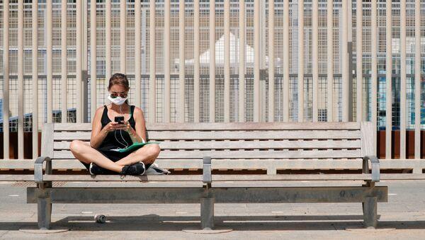 Una joven con una mascarilla en España - Sputnik Mundo