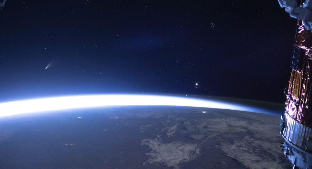 Imagen publicada por la NASA del cometa Neowise, a la izquierda, se ve en el horizonte oriental sobre la Tierra. Imagen tomada desde la Estación Espacial Internacional el 5 de julio de 2020