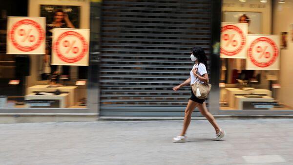Una mujer con una máscara facial pasa junto a una tienda cerrada en la ciudad de Lleida. 13 de julio de 2020 - Sputnik Mundo