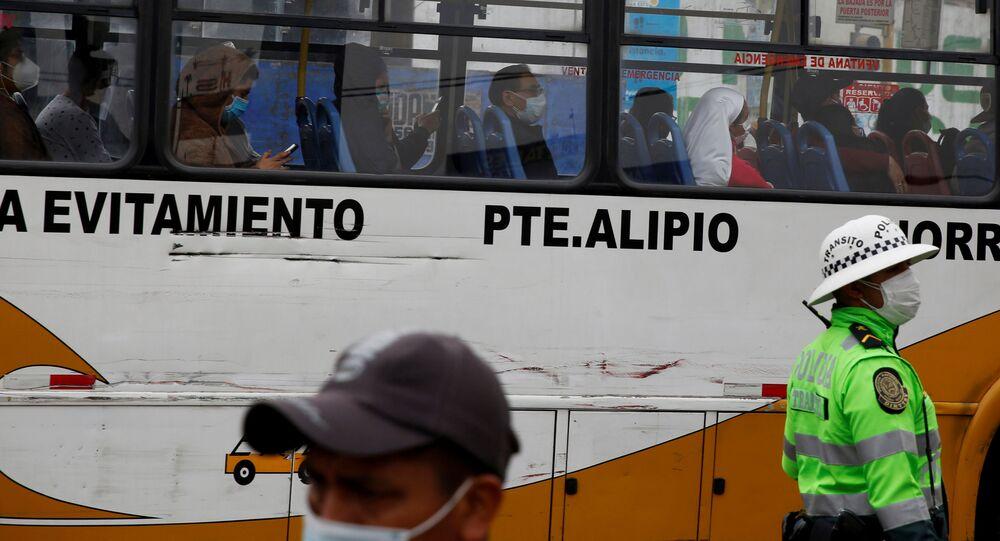Pasajeros llevan mascarillas en un bus en Lima