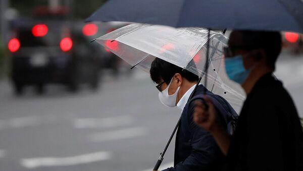 Dos hombres con mascarillas durante una nueva propagación del coronavirus en Tokio, Japón - Sputnik Mundo