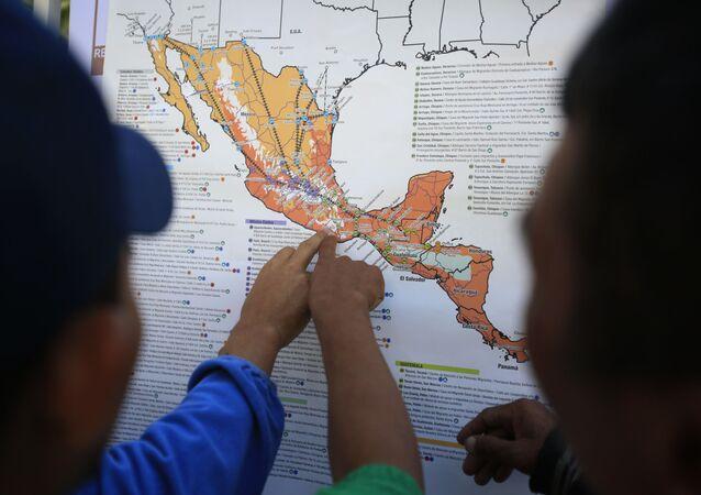 Migrantes centroamericanos planean su recorrido con un mapa en Ciudad de México