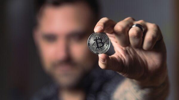 Una persona con una moneda de bitcóin - Sputnik Mundo