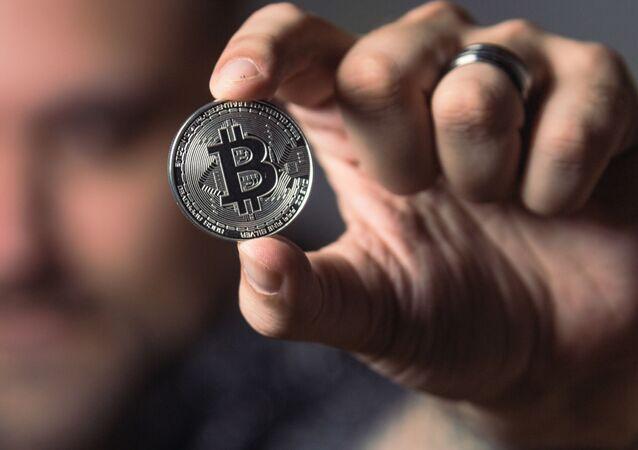 Una persona con una moneda de bitcóin