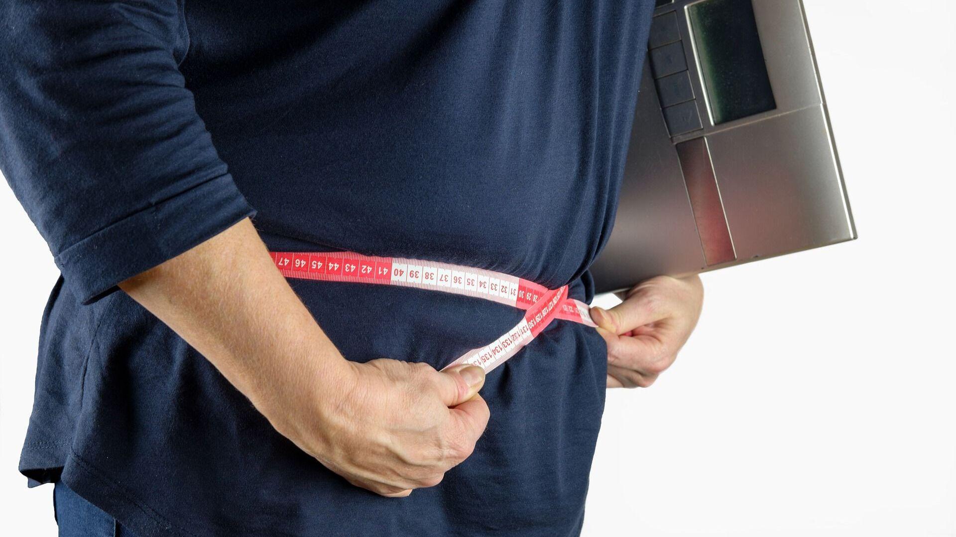 Una persona mide la circunferencia de su cintura con una cinta métrica - Sputnik Mundo, 1920, 13.06.2021