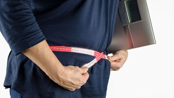 Una persona mide la circunferencia de su cintura con una cinta métrica - Sputnik Mundo