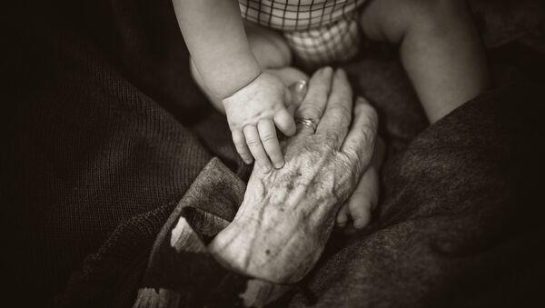 Las manos de un bebé y de una persona mayor - Sputnik Mundo