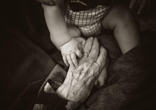 Las manos de un bebé y de una persona mayor
