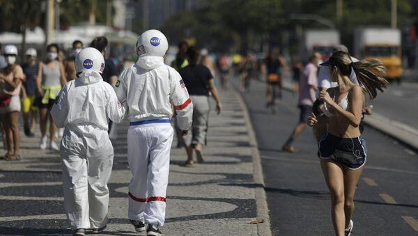 Los brasileños Tércio y Alicéia pasean por una playa en Río de Janeiro con sus trajes de astronauta - Sputnik Mundo