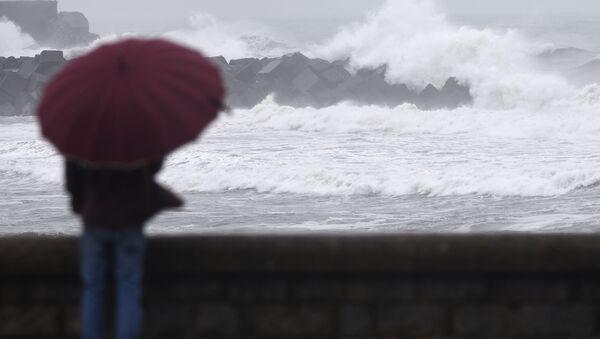 Un hombre con el paraguas mira la costa de San Sebastián durante una tormenta - Sputnik Mundo
