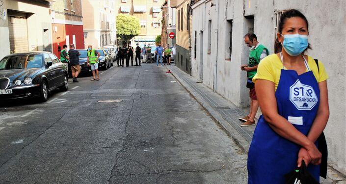 Una asistente al desahucio de Vallecas, en Madrid, esperando con la policía al fondo