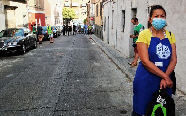 Una asistente al desahucio de Vallecas, en Madrid, esperando con la policía al fondo - Sputnik Mundo