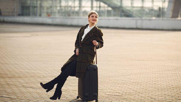 Una joven con una maleta - Sputnik Mundo