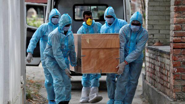 Los trabajadores médicos portan el cuerpo de un muerto por coronavirus en la India - Sputnik Mundo